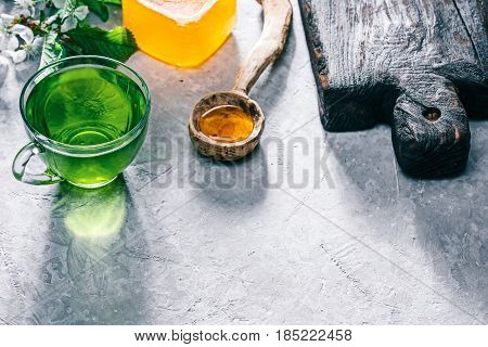 Green mint tea in translucent glass tea cup and honey in rustic spoon on concrete background. with blossom twig of pear tree and wood serving board