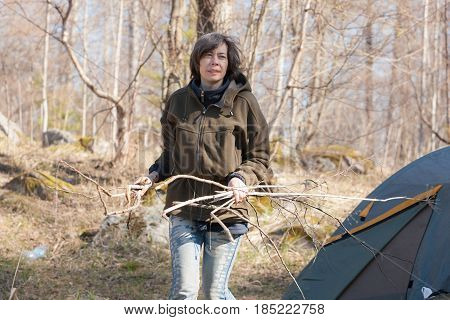 woman collects firewood for a fire in the forest