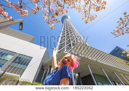 Happy tourist under the popular Tokyo Skytree in Sumida Disttrict, Tokyo, Japan, during the full bloom of cherry blossoms. Travel and tourism asia concept.