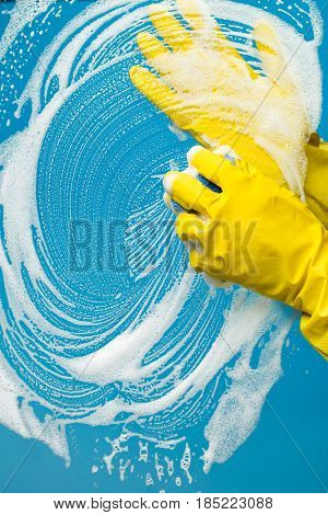 Window cleaner in rubber gloves washes
