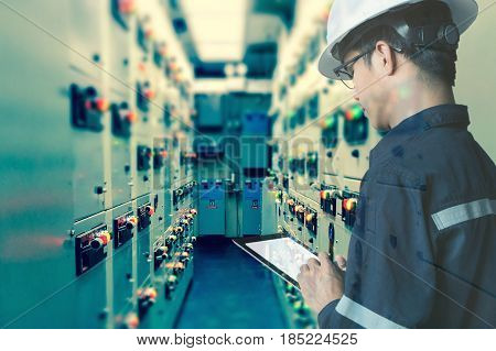 Double exposure of Engineer or Technician man working with tablet in switch gear electrical room of oil and gas platform or plant industrial for monitor process business and industry concept