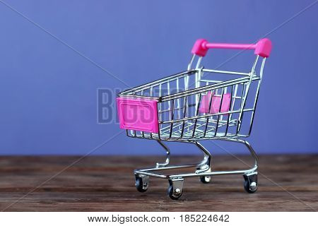 metal toy mini handcart for supermarket on a purple background.