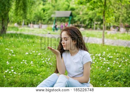 Girl sits in the park on the grass and blows off the flower petals from her palm