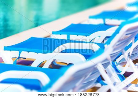 Creative abstract travel tourism and summer vacation holidays activity concept: macro view of chaise longue beach chairs and swimming pool with blue water in tropical spa resort hotel with selective focus effect