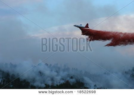 Slurry bomber dropping retardant on a  forest fire