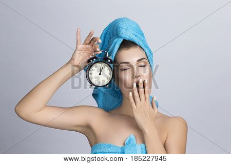 Tired yawning woman in towel on head and creme on face holding alarm clock showing midnight night creme skincare concept