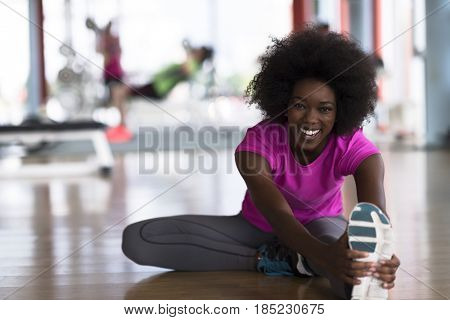 happy young african american woman in a gym stretching and warming up before workout young mab exercising with dumbbells in background