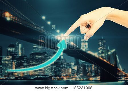 Hand pointing at creative upward arrow on night city background. Success concept