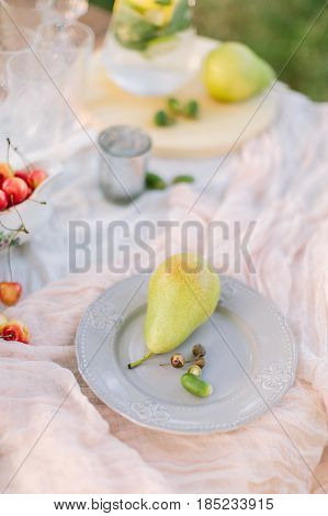 picnic, food, holiday concept - on clean white festive plate lies a beautiful ripe pear and a sprig of oak with acorns, decorated crockery at a laid table with white tablecloth and red cherries.