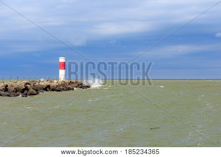 Red and white lighthouse on Lake Ontario, near Rochester, New York, on a stormy evening