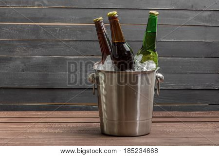 Ice bucket with beer on wooden table