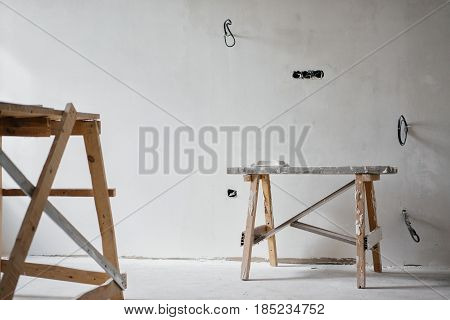 Repair in the apartment. Construction grunge ladder in white interior of a bright room with fresh plastered walls. White walls in a building construction house.