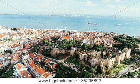 Aerial panoramic view over Lisbon in beautiful sunset sunshine.Saint George castle,downtown and neighbourhood of Alfama,river Tagus in european capital,Lisbon,Portugal.Aerial travel photography