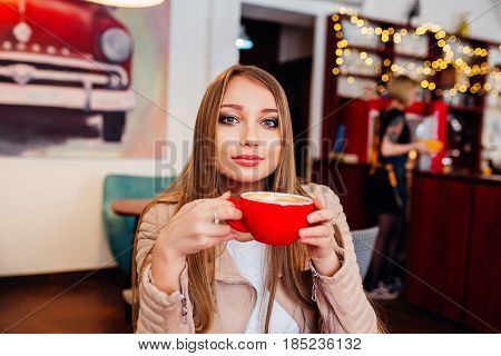 Beautiful young woman with a red cup of coffee at a cafe. Woman drinking hot latte coffee at cozy coffee shop . nice business woman lunch in modern cafe during her work break