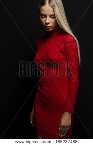 Portrait of beautiful young woman in a red dress with long blond hair standing and looking down over black background
