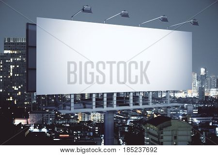 Side view of empty billboard on illuminated night city background. Advertisement concept. 3D Rendering