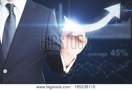 Businessman drawing bright upward arrow on dark background with business chart. Financial growth concept
