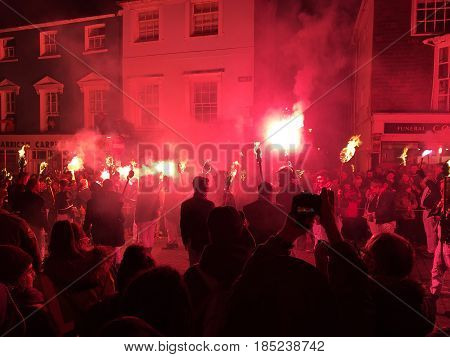 Lewes England - 5 November 2016: Dark and crowded streets of Lewes are covered in smoke due to the explosions and fire parade of the yearly celebration of the Bonfire night festivities.