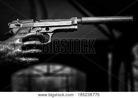 The hand holds the gun. Pistol with a silencer. Black and white image.