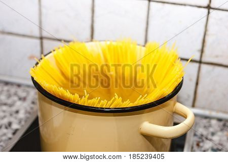 spaghetti inserted into a pot to boil water