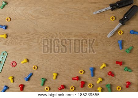 Kids Toys Background Frame Boarder with colorful toy tools on wooden table. Copy space for text. Top view. Flat lay.