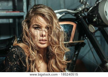 Adorable Girl Sitting At Metallic Motorcycle