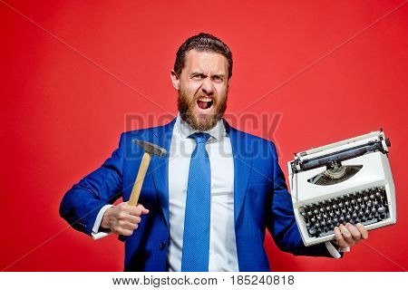 aggressive businessman hold hammer on red background business man with typewriter failure and challenge crisis and problem stress and overtime