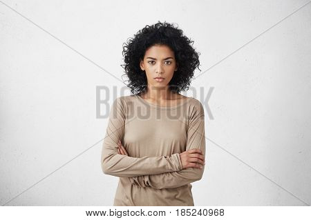 Indoor Shot Of Angry Grumpy Young Mixed Race Female Dressed Casually Keeping Arms Folded, Looking At