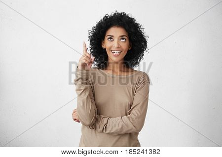Look At That! Indoor Studio Portrait Of Cheerful Attractive Casually Dressed Young Female With Curly