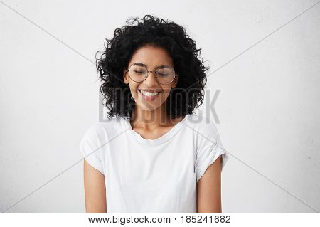 Portrait Of Charismatic And Charming Young African Woman With Curly Hair Wearing Sylish Spectacles,