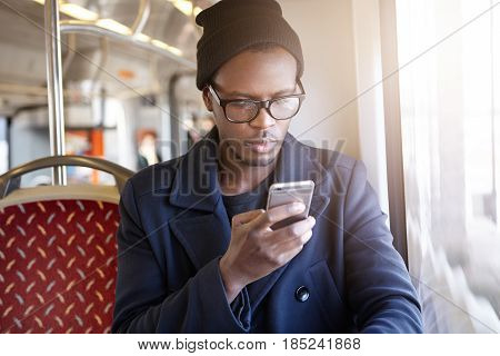 Trendy Looking Young Black European Manager In Eyewear And Hat Typing Message On Cell Phone While Us