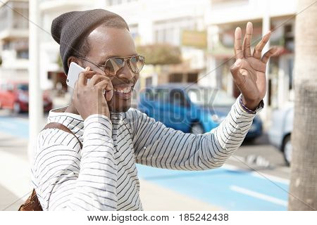 Happy African Hipster On Vacation, Walking Down Street In Morning While Talking On Phone With Girlfr