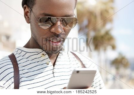 Handsome Dark-skinned Guy In Stylish Sunglasses Flirting Online With His Girlfriend Using Web-enable