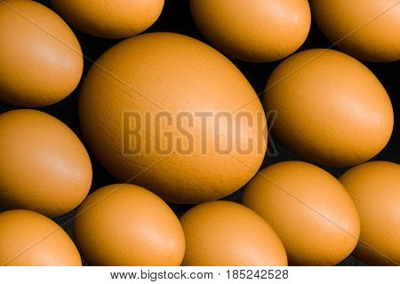 Natural background - hen eggs located on dark surface.