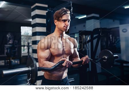 Muscular bodybuilder guy doing exercises on biceps with big dumbbell in gym