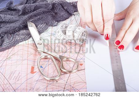 Close up hands of a fashion designer at work with cloth fabric. Female hands at work with ruler for new cloth.