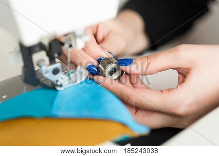 needlework and quilting in the workshop of a tailor on white background - close-up on the hands of the tailor inserting a thread bobbin for sewing machine
