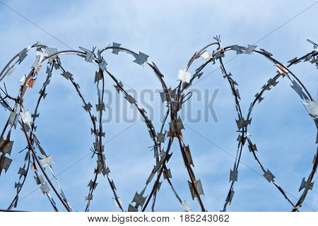 Rusty barbed wire with blades twisted into a spiral against the blue sky