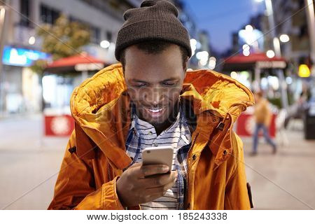 Attractive Young Black European Man In Winter Clothing Typing Text Message On His Mobile, Standing I