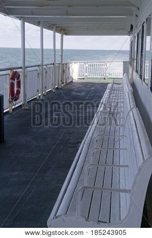 Ferry Deck with benches fencing and a life preserver as it crosses the ChesapeakeBay on a sunny day