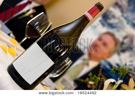 bottle of wine with blank label on table with glasses and man out of focus in background