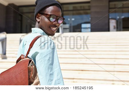 Fashionable Young Dark-skinned Man Tourist With Backpack Posing Against Modern Office Building On Co