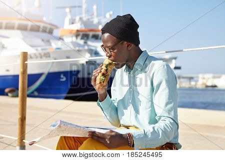 Hungry Afro American Male Tourist In Trendy Clothing And Accessories Eating Sandwich, Having Rest In