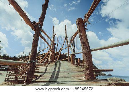 Wooded bridge to a tropical beach
