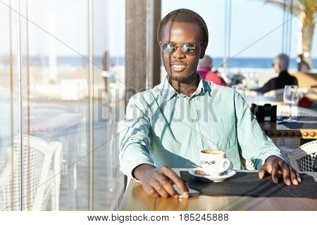 Handsome Positive Young Afro American Man Wearing Mirror Lens Sunglasses And Hat Sitting Alone At Ca