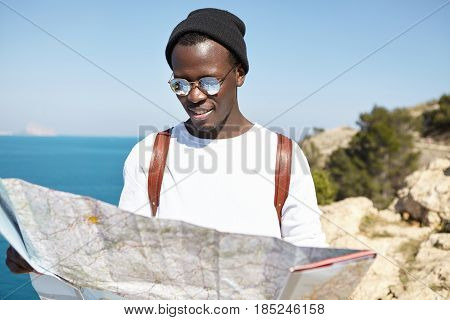 Outdoor Summer Portrait Of Stylish Traveler In Headwear And Hat Looking At Map In His Hands While Go