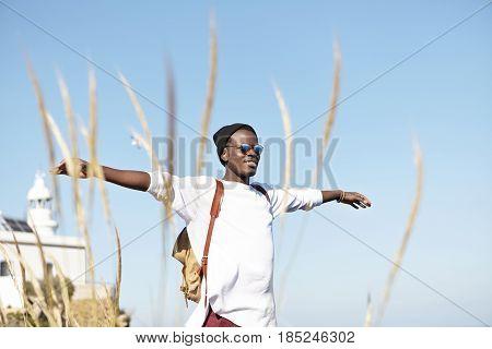 Cheerful Stylish Young Afro American Tourist With Knapsack Wearing Hat And Stylish Sunglasses Spendi
