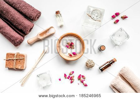 spa set with towels and organic soap on white table background top view
