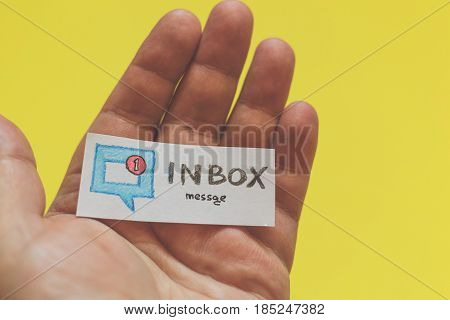 Male hand with a piece of paper and the word : Inbox message on a yellow background. Social media and network concept