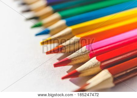 Color pencils on white paper background with perspective, selective focus. Macro or close up image
